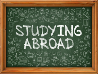 Studying Abroad - Hand Drawn on Chalkboard. Studying Abroad with Doodle Icons Around.