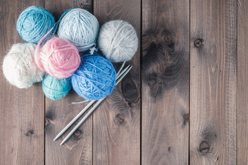 colorful yarn for knitting on a brown wooden table