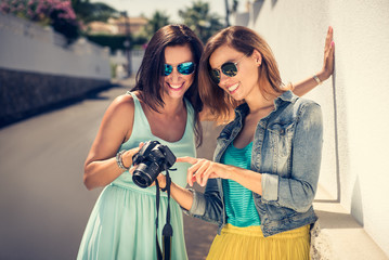 Outdoor lifestyle fashion portraits of two sisters in modern, colorful clothes, with digital camera. Two best friends hugs and posing at the street, having fun at nice sunny day.