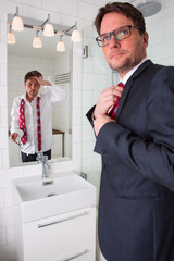 A man is looking in to his reflection in the mirror at the bathroom. The reflection is tired and the man is dressed up for a late night out or is going to work.