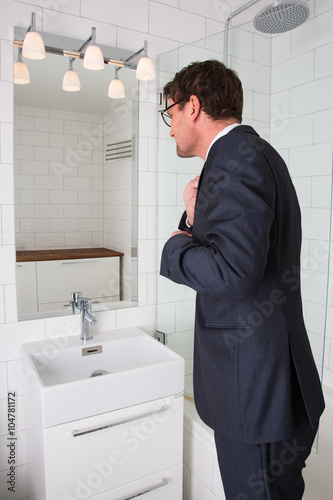 A Man Is Looking In To His Reflection The Mirror At Bathroom Tired And Dressed Up For Late Night Out Or Going