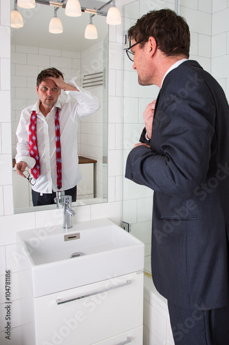 mirror reflection different person. a man is looking in to his reflection the mirror at bathroom. different person