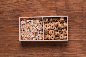 cereals and oat flakes in wooden box on brown wooden table - top