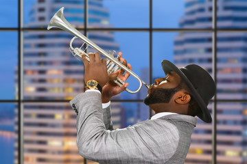 Afro trumpeter on city background.