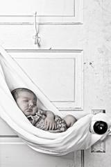 newborn baby sleeping snuggled in cloth hanging from door