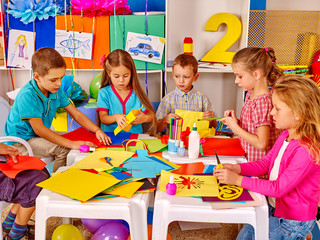 Group kids together engaged in creativity on colored paper  in kindergarten .