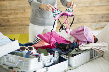 Women have put a bathing suit on a suitcase in the room