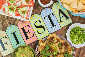 Mexican fiesta table with nachos, tortilla chips, quesadillas, guacamole dip.