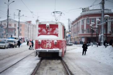 Красный трамвай идет по породу зимой. Белые улицы