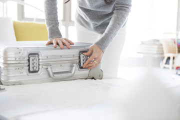 Women are multiplied by the lock on the suitcase on the bed