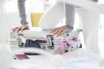 Women are holding with a foot on the suitcase