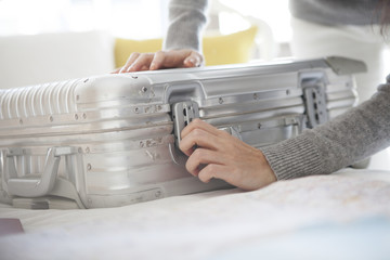 Women are closing the suitcase