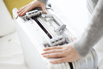 Woman is trying to Shimeyo a suitcase