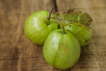 Closeup Three Ripe Green Guavas on Brown Table
