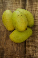 Top View of Four Mangos on Wooden Table