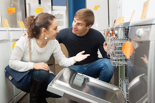 family couple at household appliances store