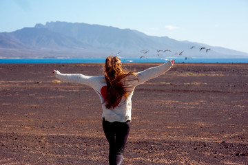 Carefree woman running forward to the ocean and mountains with birds flying on the background on Fuerteventura island in Spain