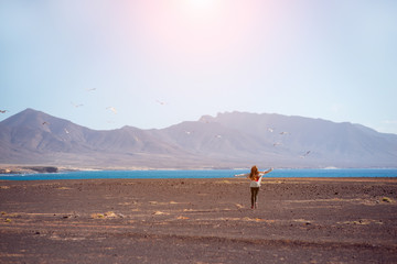 Carefree woman running forward to the ocean and mountains with birds flying on the background on Fuerteventura island in Spain. Wide angle view with copy space