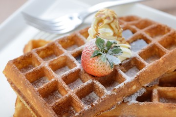 Strawberry and whipped cream on a crisp golden waffle