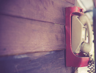 Retro phone on a wooden wall,vintage color toned image