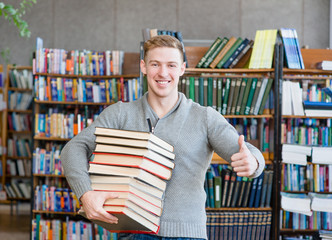 student with pile books showing thumbs up in college library