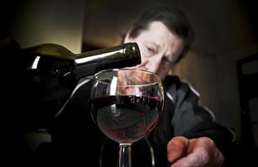 Bicchiere di vino rosso, sullo sfondo uomo anziano