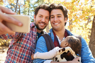 Gay Male Couple With Baby Taking Selfie On Walk In Woodland