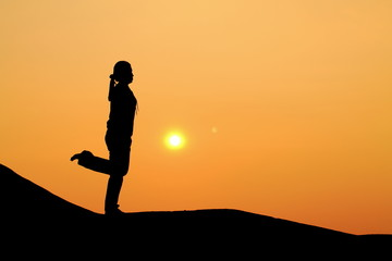 Silhouette picture of a woman plays yoga on the hill
