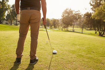 Close Up Of Male Golfer Lining Up Tee Shot On Golf Course