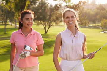 Two Female Golfers Walking Along Fairway Carrying Clubs