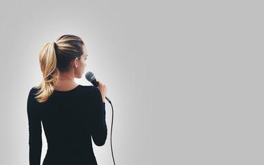Ragazza con microfono parla canta
