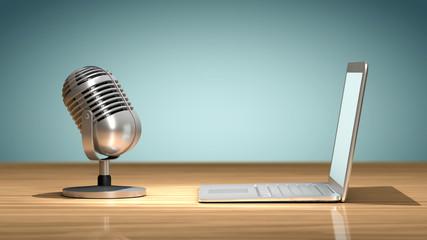Microphone vintage face à un ordinateur portable posés sur une table en bois, orienté et prêt pour enregistrer