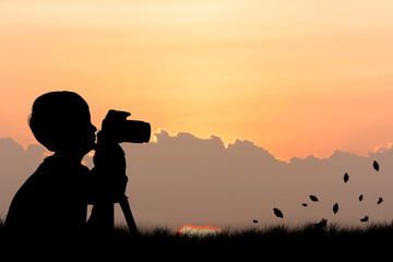 Silhouette of little boy taking camera sunset background