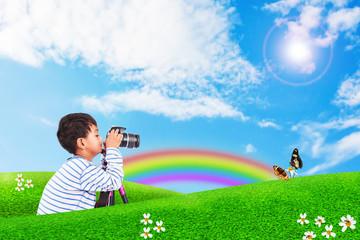 little boy taking camera on nature background