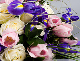 Delicate beautiful bouquet of  iris, roses and other flowers in
