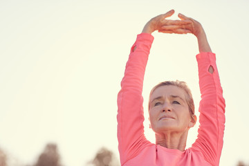 Senior woman stretching arms before early morning outdoor exerci