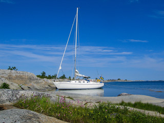 Moored sailboat at small archipelago island in the sun