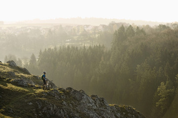Germany, Bavaria, Young man mountainbiking at sunrise