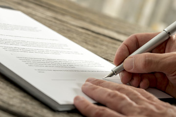 Closeup of male hand signing a contract or application form