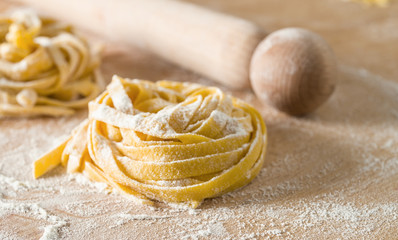 raw egg pasta with flour and rolling pin