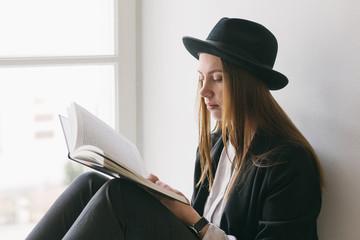 Woman reading beside a window
