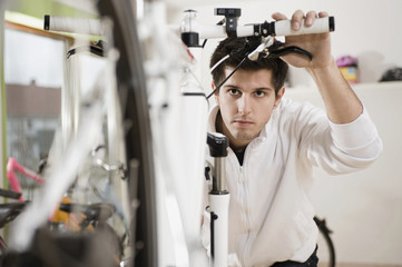 Germany, Bavaria, Young man working on bicycle