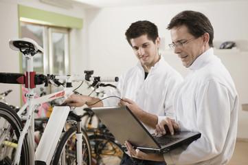 Germany, Bavaria, Mechanics testing electric bicycle with laptop