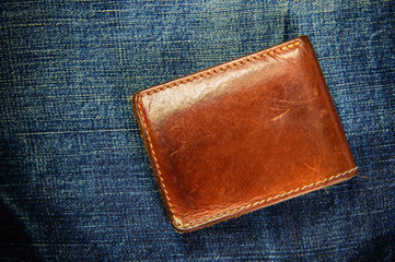 Brown leather wallet on jeans background