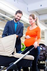 Paar im Babyladen kauft Kinderwagen beim Babyaustatter Laden, die Frau ist schwanger