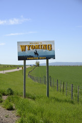 Welcome to Wyoming / Welcome to Wyoming state sign  with the Wyoming landscape of open plains and mountains in the background.
