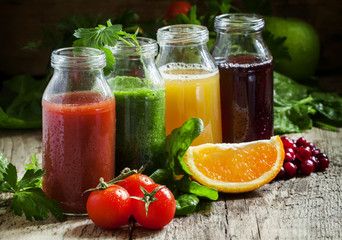 Bottles with fresh juices from fruits and vegetables on an old w