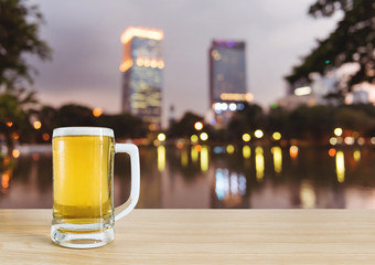 frosty glass of light beer for drinking on wooden with blurry city light in park at night