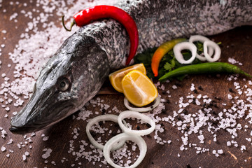 Delicious fresh fish with aromatic herbs, spices and vegetables on dark vintage background