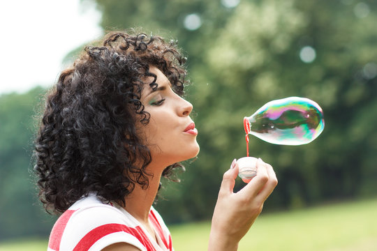 Portrait of beautiful woman blowing bubbles in park.